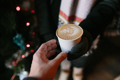 Coffee for you with love. Someone gives another person a cup of hot drink stock photography
