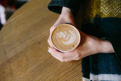 Coffee for you with love. Someone sits at the table and holding a hot drink royalty free stock image