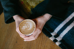 Coffee for you with love. Someone sits at the table and holding a hot drink royalty free stock photo