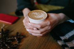 Coffee for you with love. Someone sits at the table and holding a hot drink royalty free stock photos