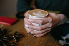 Coffee for you with love. Someone sits at the table and holding a hot drink stock photography