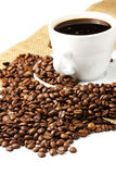 Coffeebeans near coffee cup. And jute on white background stock photos