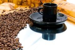 Coffeebeans y taza en el espejo Imagen de archivo libre de regalías