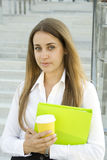 Coffeebreak. Business woman with a green folder and paper cup of coffee royalty free stock photo
