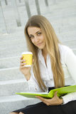 Coffeebreak. Business woman with a green folder and paper cup of coffee stock images