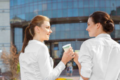 Coffeebreak of two colleagues. Two attractive businesswoman having a coffeebreak outdoors Royalty Free Stock Image