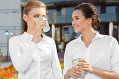 Coffeebreak of two colleagues. Two beautiful businesswoman having a coffeebreak outdoors Royalty Free Stock Photo