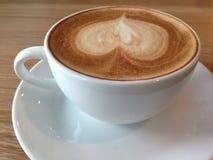 Coffeecup av med hjärtaformkonst på skum Arkivbilder