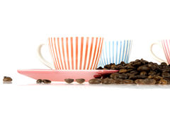 Coffeecup and beans. A coffeecup with a lot of coffeebeans on white Royalty Free Stock Images
