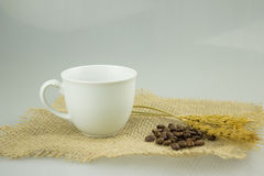Coffeecup with coffeebeans on gunny textile Royalty Free Stock Photos
