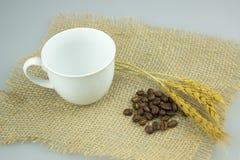 Coffeecup com coffeebeans na matéria têxtil do gunny Fotografia de Stock Royalty Free