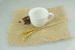 Coffeecup com coffeebeans na matéria têxtil do gunny Foto de Stock