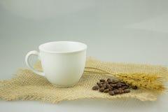 Coffeecup com coffeebeans na matéria têxtil do gunny Fotos de Stock Royalty Free