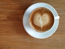Coffeecup of with heart shape art on foam. Coffee cup table wood top view Stock Photography