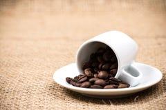 Coffeecup med coffeebeans på säckvävtextilen Royaltyfri Foto