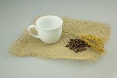 Coffeecup med coffeebeans på säckvävtextilen Arkivfoto