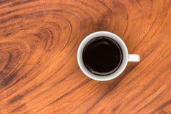 Coffeecup med kaffe i den på ett trä bordlägger Arkivfoto