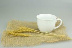 Coffeecup med vete på säckvävtextilen Arkivbild