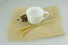 Coffeecup mit coffeebeans auf Juteleinwandgewebe Stockfoto