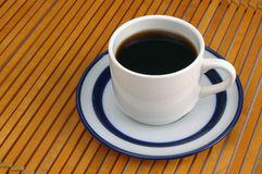 Coffeecup on Wood. Coffee cup and saucer on wood slat place-mat Stock Image