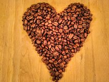 Coffee Beans In The Shape Of A HeartOn Wood Background stock photos