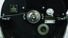 Επαγγελματικό coffeemachine και ακατέργαστα φασόλια καφέ Τα άσπρα φασόλια καφέ είναι τηγανισμένα σε μια επαγγελματική μηχανή για  φιλμ μικρού μήκους
