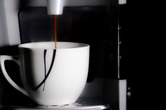 Coffeemachine is producing a hot espresso in a white cup. Royalty Free Stock Images