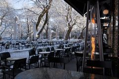 Coffees shops tables chairs in the snow ice winter season trees road in Ioannina city Greece. Coffees shops tables chairs in the snow ice in winter season in royalty free stock image