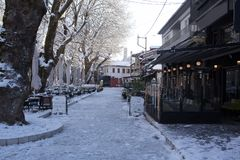 Coffees shops tables chairs in the snow ice winter season trees road in Ioannina city Greece. Coffees shops tables chairs in the snow ice in winter season in stock photo