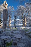 Coffees shops tables chairs in the snow ice winter season trees road in Ioannina city Greece. Coffees shops tables chairs in the snow ice in winter season in stock image