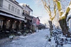 Coffees shops tables chairs in the snow ice winter season trees road in Ioannina city Greece. Coffees shops tables chairs in the snow ice in winter season in royalty free stock photos