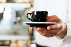 Coffeeshop - barista presents coffee or cappuccino Royalty Free Stock Photo