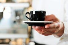 Coffeeshop - barista stellt Kaffee oder Cappuccino dar lizenzfreies stockfoto