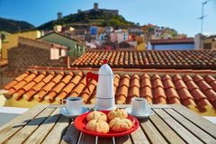 Coffee and Italian sweets with view to Bosa village, Sardinia, Italy Stock Images