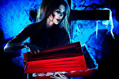 Coffin. Bloodthirsty witch standing at the night cemetery and holding a coffin Royalty Free Stock Photo