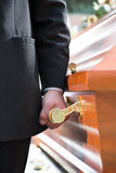 Coffin bearer carrying casket at funeral Stock Photography
