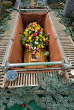 Coffin with bouqet of flowers in a grave Stock Image