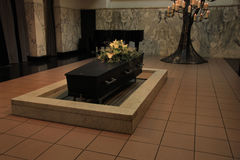 Coffin with funeral flowers. Wooden casket with funeral flowers in a crematorium hall stock photos