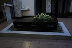 Coffin with funeral flowers. Wooden casket with funeral flowers, cremation ceremony royalty free stock image