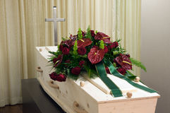 Coffin in morgue. A coffin in a morgue with cross and a flower arrangement Stock Images