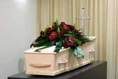 Coffin in morgue. A coffin in a morgue with cross and a flower arrangement Stock Photography