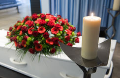 Coffin in morgue. A coffin with a flower arrangement in a morgue and a burning candle in front Royalty Free Stock Photo