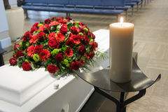 Coffin in morgue. A coffin with a flower arrangement in a morgue and a burning candle in front Stock Photography