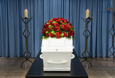 Coffin in morque. A coffin with a flower arrangement in a morgue and a burning candle in front Royalty Free Stock Photography