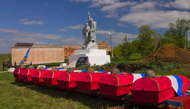 The coffins covered with flags containing the remains of Soviet soldiers at the monument to soldiers and dug graves. Burial. Royalty Free Stock Images