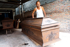 Coffins. Craftsman is finalizing a coffin in the city of Solo, Central Java, Indonesia Stock Photos