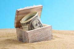 Coffre avec l'Américain d'argent cent billets d'un dollar sur une plage Photo libre de droits