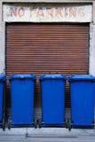 Coffres d'ordures bleus stationnés dans une zone de stationnement de numéro photographie stock