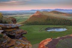 Coffres de chaîne de montagne pendant un lever de soleil coloré dans la République de Khakassia, Russie Les gens admirent le leve Photographie stock libre de droits