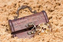 Cofre del tesoro con el oro en una playa arenosa Imagenes de archivo